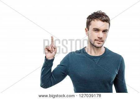 Portrait of stylish handsome young man isolated on white background. Man pointing up and looking at camera. Free space for logo
