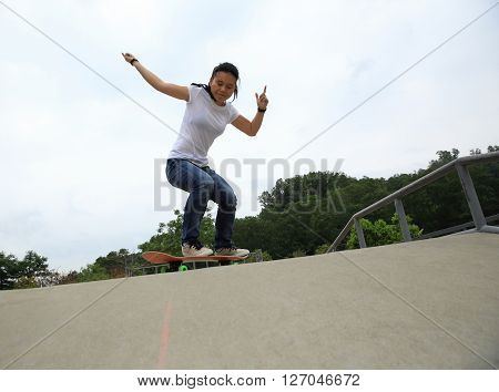 young woman skateboarder practice ollie at skatepark