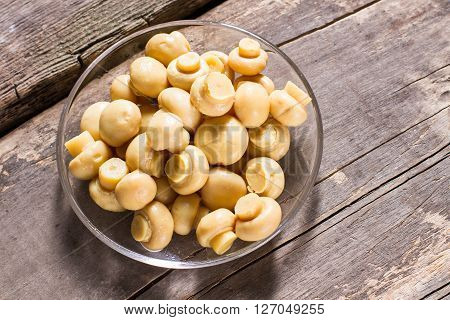 Champignons in glass bowl. Mushrooms on old wooden background. Special recipe for marinated champignons. Enjoy the taste.