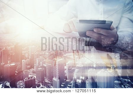 Double exposure photo.Man touching modern tablet.Using electronic device.City skyscrapers background, film and bokeh effects
