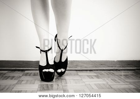 Young sexy woman feet with black high heels close up on white wall