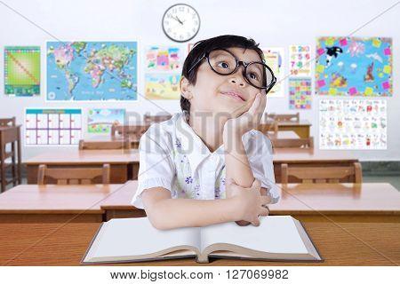 Portrait of a pensive elementary school student sitting in the classroom with a book on desk and wearing glasses