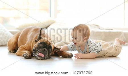 Little baby boy with boxer dog lying on the floor at home