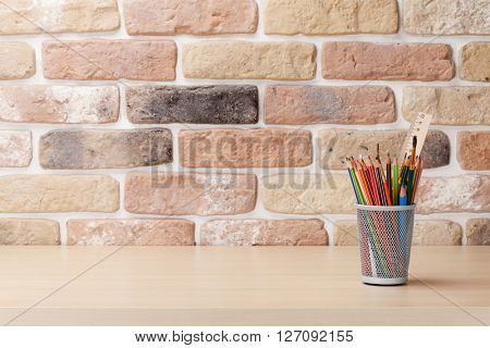 Office desk workplace table in front of brick wall. View with copy space