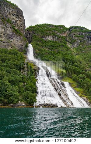 Waterfall called The Suitor flowing into Geirangerfjord Norway