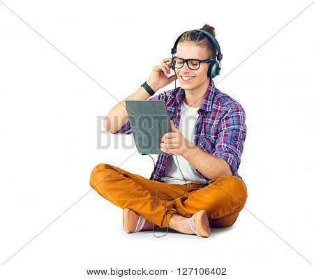 Young fashion man sitting on the floor and enjoying music with his headphones. Handsome young stylish hipster guy in headphones holding tablet pc and listening music, isolated on a white background