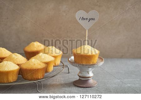 Homemade vanilla cupcake with a handcrafted cake pick on rustic mini cake stand