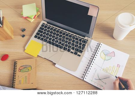 Male hand drawing business diagrams on desktop with laptop and office tools