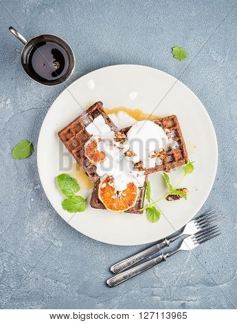 Belgian soft waffles with blood orange, cream, marple syrup and mint  on white plates over concrete textured background. Top view, vertical