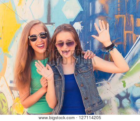 Two funny affectionate teenagers friends laughing and having fun outdoors. Bright stylish lifestyle urban portrait.