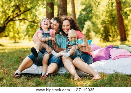 Young happy family with kids having picnic with colored pillows outdoors. Parents with two children relax in a sunny summer garden. Mother father little girl and baby boy playing in park.