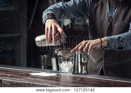 Barman makes cocktails with a shaker closeup.