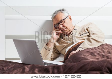 Senior man is lying in bed and he fell asleep while using laptop