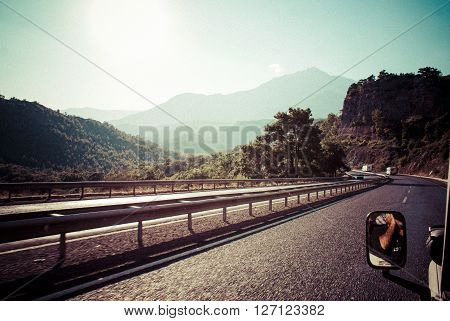 The road in the mountains. The car rides on the highway.
