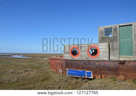 Rusty old Houseboat overlooking estuary east anglia