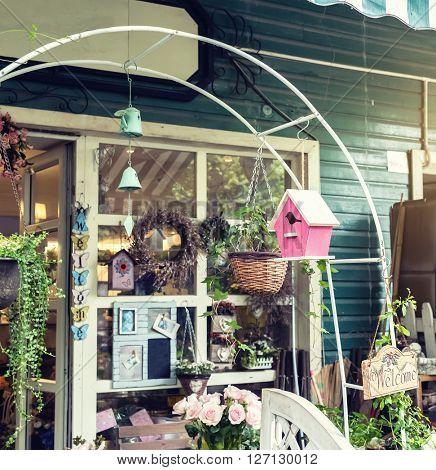 cafe with birdhouse nestles,glass bottle,flower
