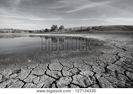 Drought. Chapped ground in foreground. Coast of ephemeral impounded body. Black-and-white image.