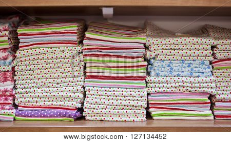 Stacks of colored terry dishcloths on the shelves in a shop.