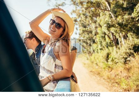 Attractive young woman in the back of pickup truck with friends. Young people on a road trip.