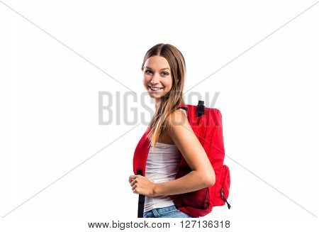 Beautiful student in white singlet with red schoolbag. Studio shot on white background, isolated.