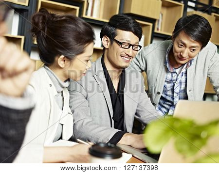 a team of young asian business people working together using laptop computer happy and smiling.