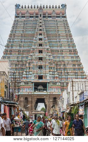 Trichy India - October 15 2013: Frontal view on the massive Rajagopuram of Ranganathar Temple. View from street leading to the tower inside the temple perimeter. Plenty of people and small shops in the picture.