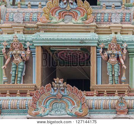 Trichy India - October 15 2013: Detail of the massive Rajagopuram of Ranganathar Temple. Focus on one opening protected by Dwarapalakas holding Vishnu symbols. Pastel colors pillars and statues.