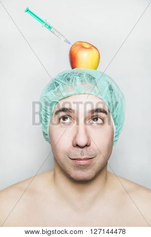 Medical patient with green cap looks with curiosity on red yellow apple with a syringe of hyaluronic acid. Apple is on his head. Picture shows hyaluronic acid is healthy natural and with vitamins.