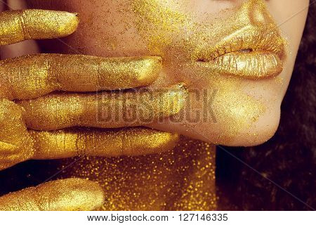 Magic Girl Portrait in Gold. Golden Makeup close-up portrait in studio shot color