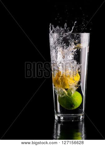 Lemon and Lime dropped into a glass of water on a black background high speed photography