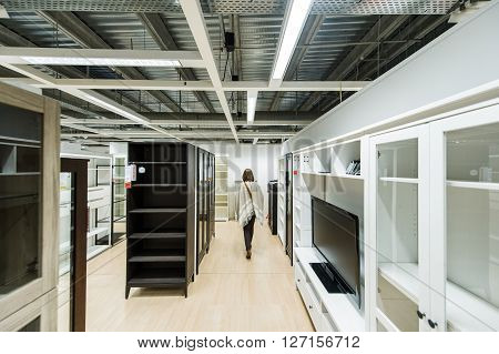 PARIS FRANCE - APR 12 2016: Woman choosing modern wardrobe furniture and closets in the modern IKEA shopping furniture mall in Paris
