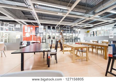 PARIS FRANCE - APR 12 2016: Woman choosing modern kitchen furniture tables and chairs in the modern IKEA shopping furniture mall in Paris