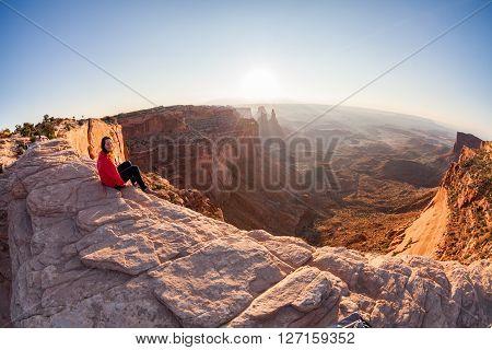Girl sitting at the Mesa Arch at sunrise Canyonlands National Park Utah