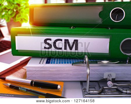 Green Office Folder with Inscription SCM - Supply Chain Management - on Office Desktop with Office Supplies and Modern Laptop. SCM Business Concept on Blurred Background. SCM - Toned Image. 3D.