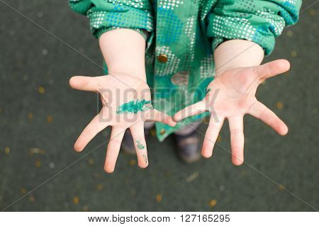 children's hands in wet paint. child touched something painted despite the sign Caution wet paint! do not touch.