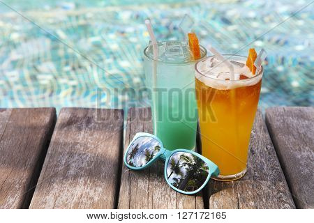 Cocktails with sunglasses near the swimming pool on the background of the water