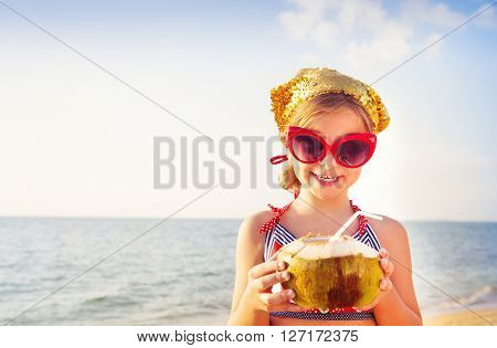 Little happy adorable girl drinking coconut milk on the beach