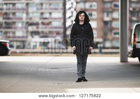 Androgynous man wearing black coat standing on parking lot