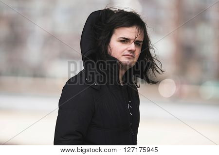 Androgynous man wearing black coat in urban residential area