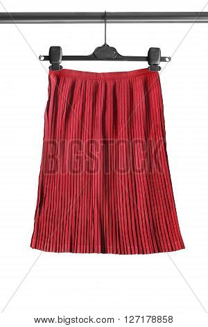 Red pleated skirt on clothes rack isolated over white