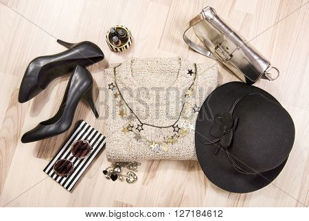 Winter sweater and accessories arranged on the floor. Woman sweater with silver accessories high heels hat necklace and nail polish.