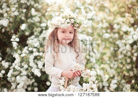 Smiling baby girl 3-4 year old holding basket with flowers outdoors. Childhood.