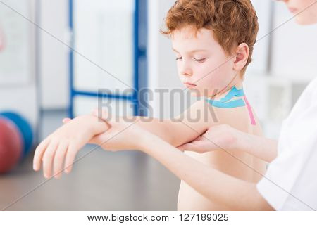 Little cute red head boy having arm problem after injury. Physical therapist treating the patient with exercises