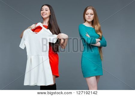 Happy cheerful young woman and envious angry female on shopping over grey background
