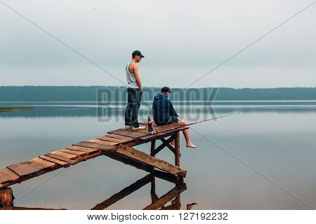Two men are waiting on a wooden bridge when the fish are biting. Weekend photo.