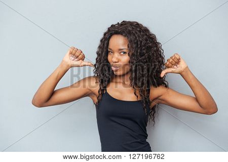 Afro american woman showing fingers at herself over gray background