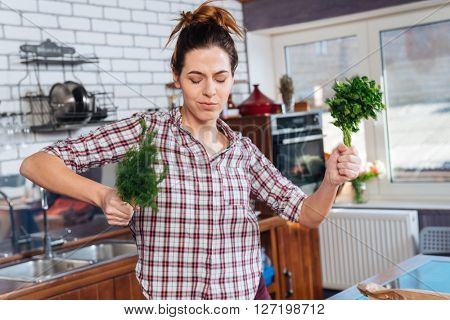 Happy young woman with eyes closed holding dill and parsley and dacing on the kitchen