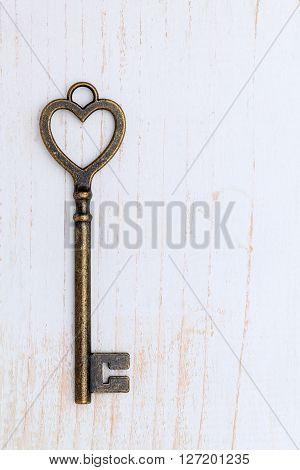 heart shaped vintage key on white wood background