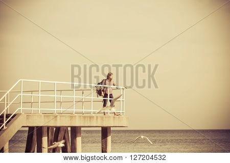 Man hiker backpacker on pier. Young guy tramping with backpack by seaside. Adventure and tourism.