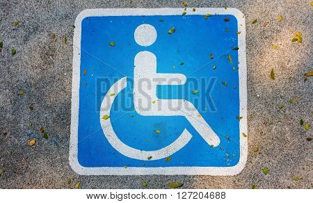 International handicapped symbol painted in bright blue on parking space